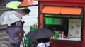 People With Umbrellas At Snack Stand In China On Rainy Day Footage