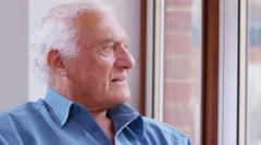 4K Portrait of smiling elderly man sitting by the window - stock footage
