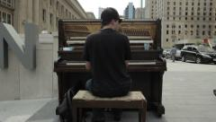 Busker plays an upright piano on the street - stock footage