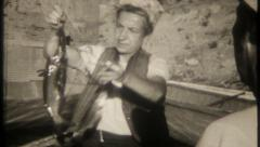 2699 - woman shows her catch, outfishes husband - vintage film home movie Stock Footage