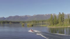 Flying Alongside Wakeboarder with Mountainous Background Stock Footage