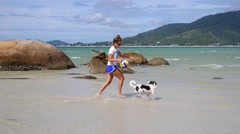 Young Woman Playing with Dog on Beach Stock Footage