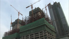 Construction cranes on skyscraper, China - stock footage