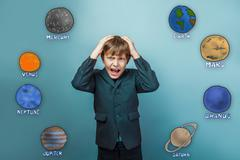 boy businessman holding his hands behind his head and his mouth - stock photo
