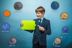 boy in a business style suit points to a bright green plate and - stock photo