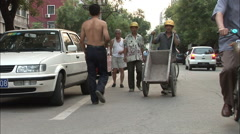 Chinese worker pushes wheelbarrow, China - stock footage