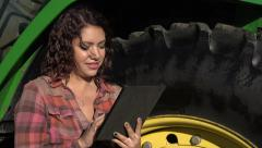 Young woman using an ipad near a tractor Stock Footage