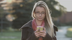 Gorgeous lady texting on smart phone at park in the city Stock Footage