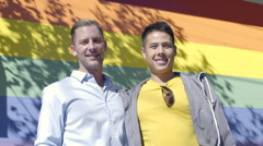 Portrait Of Happy Gay Couple, Smiling, In Front Of Gay Pride Rainbow Wall Stock Footage
