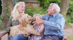 4K 3 generations of a family spending time together in garden with pet dog Stock Footage