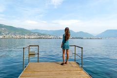 Young beautiful girl in the dress standing on pier Stock Photos