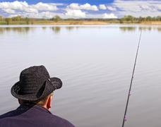 A man with a fishing rod on the river Stock Photos