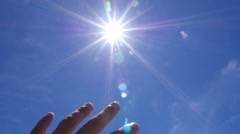 Hand to Bright Sun Against Blue Sky. Slow Motion Stock Footage