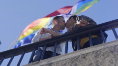 Gay Couple Hold Hands, Stand Under Huge Gay Pride Rainbow Flag Stock Footage
