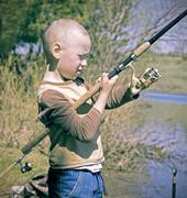 The boy spinning reel fishing rods - stock photo