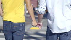 Closeup Of Gay Couple Holding Hands And Walking Across The Street In City - stock footage