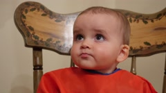 Adorable baby boy wont eat his baby food in highchair Stock Footage