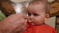 An adorable baby boy wont eat his baby food in highchair Stock Footage