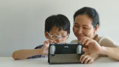 Mother with her son web surfing on digital tablet Stock Footage