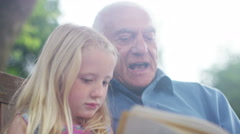 4K Grandfather & granddaughter sitting in the garden & reading together Stock Footage