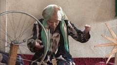 Woman spinning silk, Uyghur, China Stock Footage