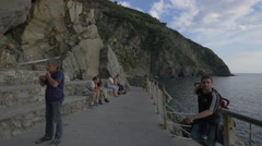 Relaxing on rocks on the seafront in Cinque Terre Stock Footage