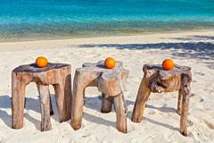 Three oranges are on original  beach tables are made from trunk of tree Stock Photos