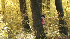 Little girl hiding behind a tree Stock Footage