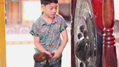 Little asian boy bangs on a large Antique Thai Gong( Bell) Stock Footage