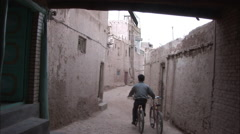 Kashgar alleyway, man on bike, China Stock Footage