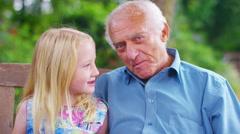 4K Grandfather & granddaughter make a video call in the garden Stock Footage