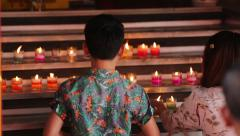 Asian family, Mother and son take lights a candle at the Buddhist temple, Stock Footage