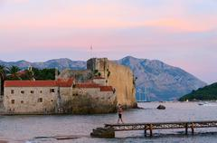 View of Citadel of Old Town of Budva and Sveti Nikola Island at sunset - stock photo