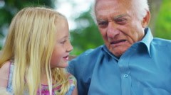 4K Grandfather & granddaughter chatting as they sit in garden  - stock footage