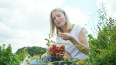 4K Beautiful woman eating freshly picked summer fruit in the countryside Stock Footage