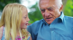 4K Grandfather & granddaughter chatting as they sit in garden  Stock Footage