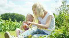 4K Happy mother & daughter eating freshly picked summer fruit in the countryside Stock Footage