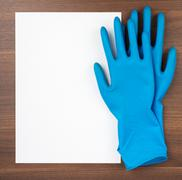Blank paper with blue rubber gloves Stock Photos