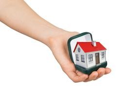 Stock Photo of Open green ring box with house in humans hand