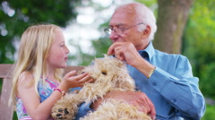 4K Grandfather & granddaughter chatting as they sit in garden with pet dog Stock Footage