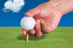 Golfer places a golf ball and tee in the ground - stock photo