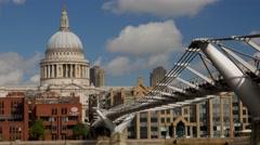 Tourists walk over the Millennium Bridge in London. - stock footage