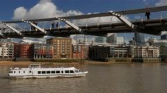 Thames River bus passes under Millennium Bridge Stock Footage