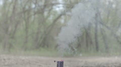 Blue smoke bomb smokes and blow out in the forest background slow motion Stock Footage