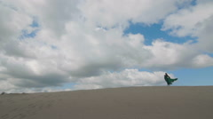 Girl stand in green dress on sand dune while wind blowing her clothes blue sky Stock Footage