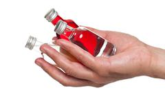 Hand holding little bottles of liquor Stock Photos