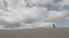 Beauty Girl in green dress stand on sand dune while wind blowing her clothes Stock Footage