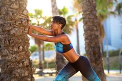 Beautiful black woman stretching workout routine - stock photo