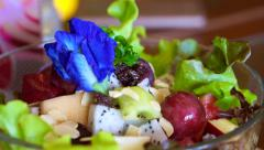 Video of purple flowers on fresh vegetables and fruits salad Stock Footage