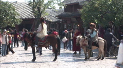 Naxi men on horses, Lijiang Old Town, China Stock Footage